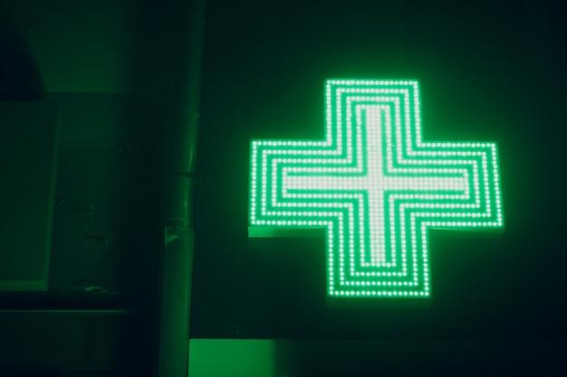 Sinal da cruz verde em um prédio de farmácia. Foto Premium