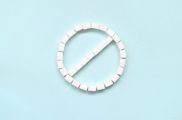 Sinal da proibição de cubos de açúcar em um fundo azul pastel