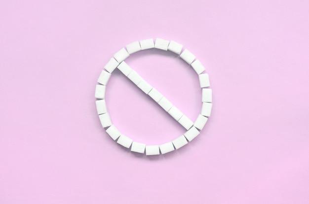 Sinal da proibição de cubos de açúcar em um rosa pastel