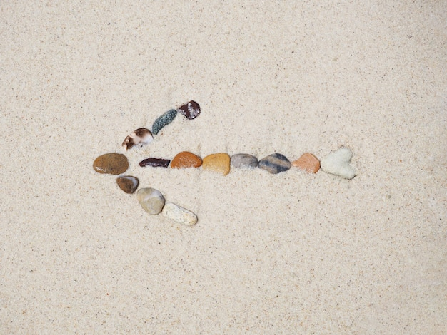 Sinal da seta das pedras na areia da praia.