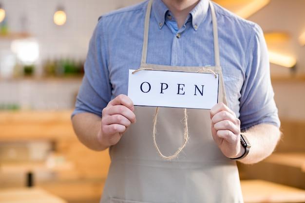 Sinal de abertura. perto de uma etiqueta com uma inscrição aberta, estando nas mãos de um trabalhador de um café bonito e simpático