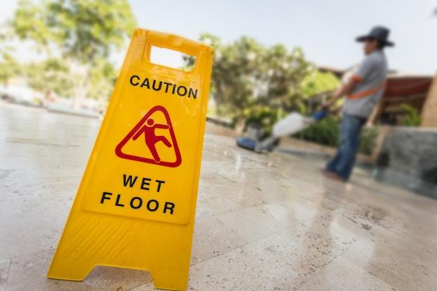 Sinal de advertência amarelo e borrão de homem fazendo polimento de chão de pedra