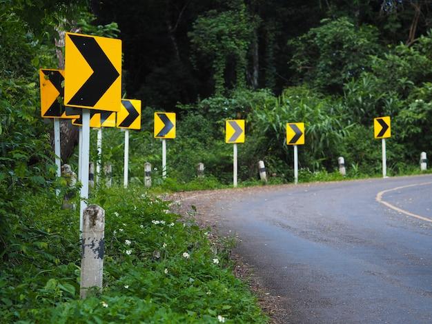 Sinal de alerta de curva em uma estrada sinuosa na floresta para dirigir com cuidado.