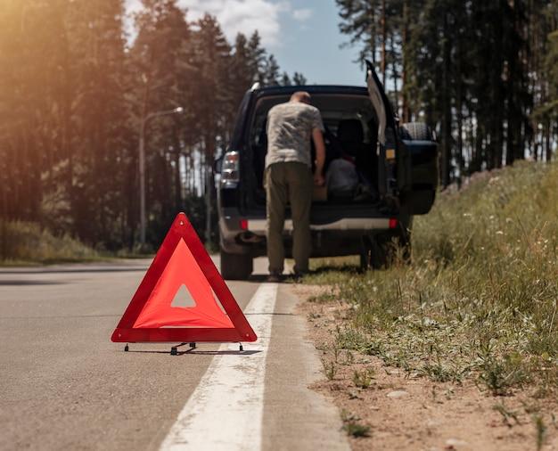 Sinal de alerta triangular na estrada perto do carro quebrado com o motorista no fundo