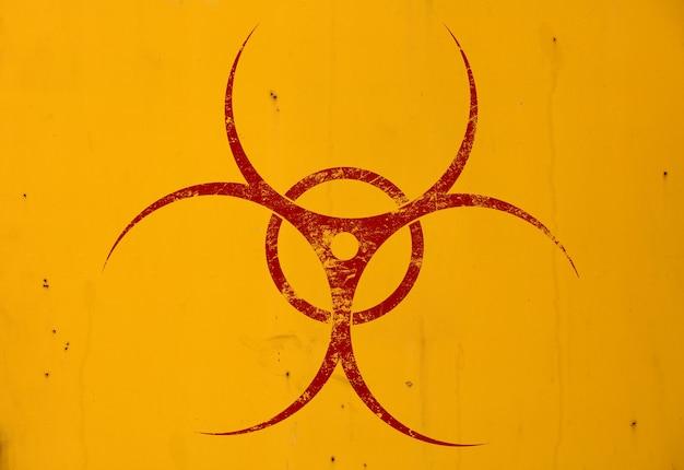 Sinal de alerta vermelho escuro de perigo biológico pintado sobre fundo amarelo grunge com espaço de cópia