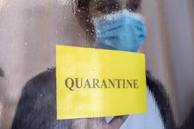 Sinal de aviso amarelo com quarentena de texto na janela. homem solitário em quarentena com covid-19 em isolamento doméstico. prevenção de pandemia de coronavírus. homem na máscara médica protetora em casa