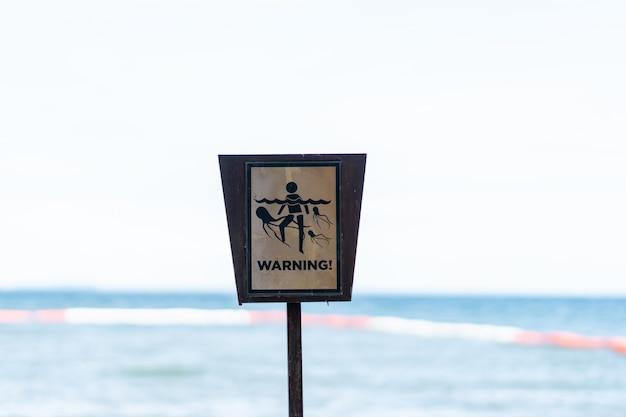 Sinal de aviso, cuidado com a água-viva na praia.