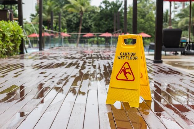 Sinal de aviso de chão molhado amarelo no chão no corredor do hotel