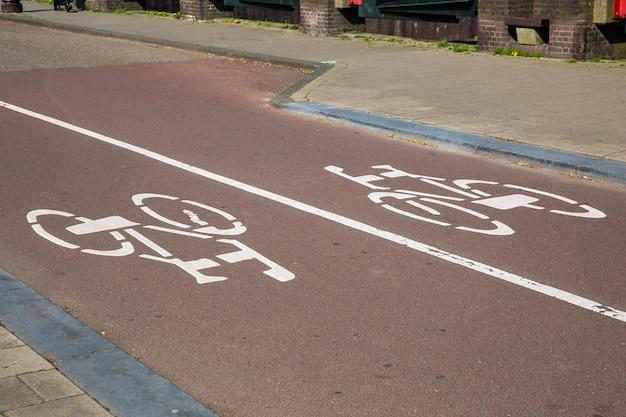 Sinal de bicicleta branco na estrada com trânsito de mão dupla