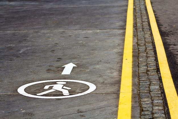 Sinal de caminho a pé na superfície da estrada de asfalto