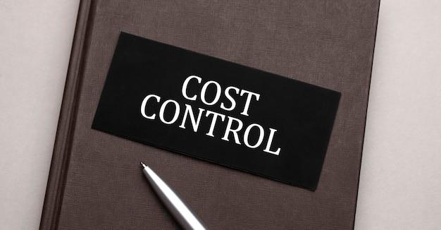 Sinal de controle de custos escrito no adesivo preto no bloco de notas marrom