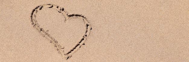 Sinal de coração desenhado na areia molhada do litoral