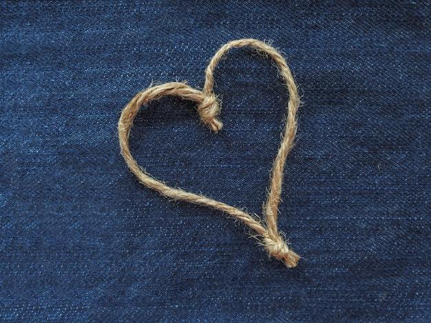 Sinal de coração feito de barbante em jeans azul. dia mundial do coração ou conceito de amor. fechar-se