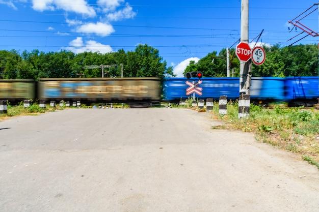 Sinal de cruzamento de ferrovia e semáforo piscando na frente do cruzamento de ferrovia. movimento borrado do trem