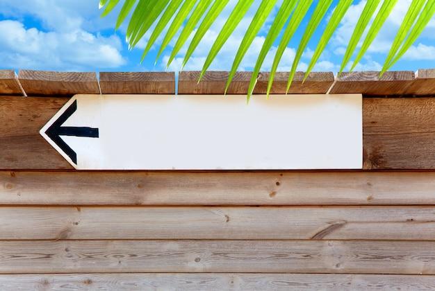 Sinal de direção de seta madeira envelhecida no céu azul