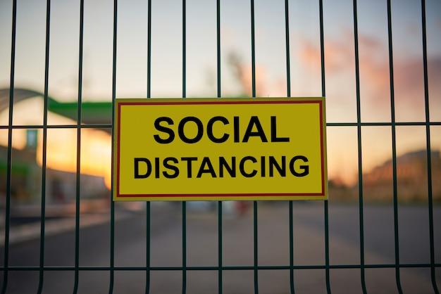 Sinal de distanciamento social em cima do muro com vista da cidade turva