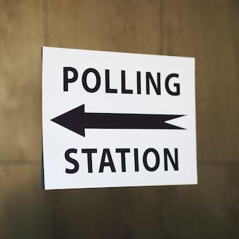Sinal de estação de voto com direção em close-up de parede de madeira