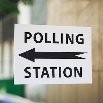 Sinal de estação de voto com direção na janela close-up