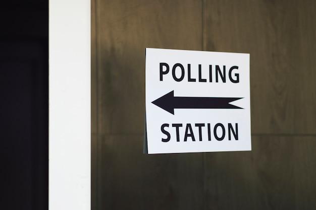 Sinal de estação de voto com direção na parede de madeira