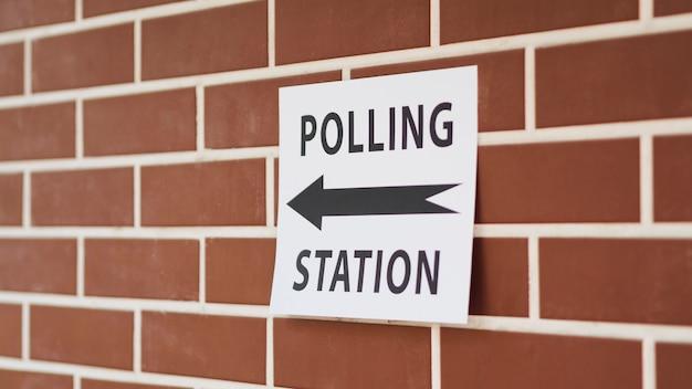 Sinal de estação de voto com direção na parede de tijolo