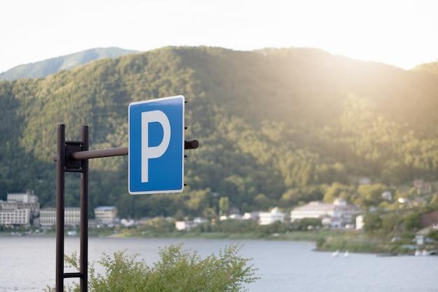 Sinal de estacionamento azul com vista para o rio de montanha e pôr do sol