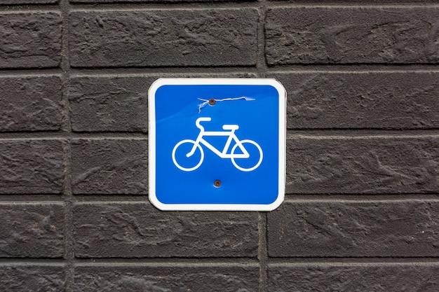 Sinal de estacionamento de bicicleta na parede de pedra