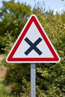 Sinal de estrada de encruzilhada triangular em um entroncamento de estrada rural