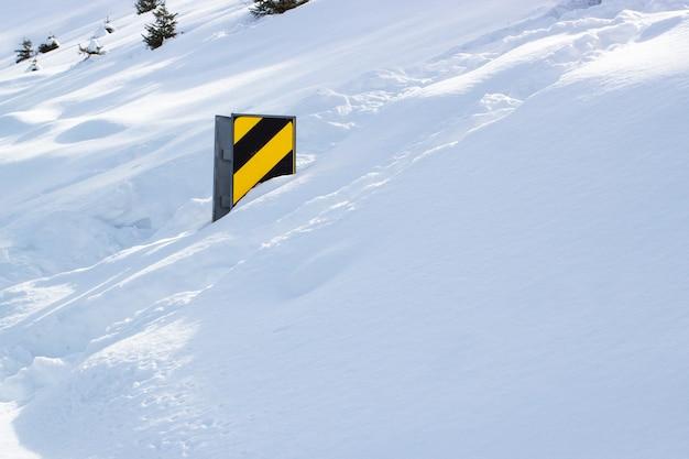 Sinal de estrada do país após forte nevasca em um dia ensolarado.