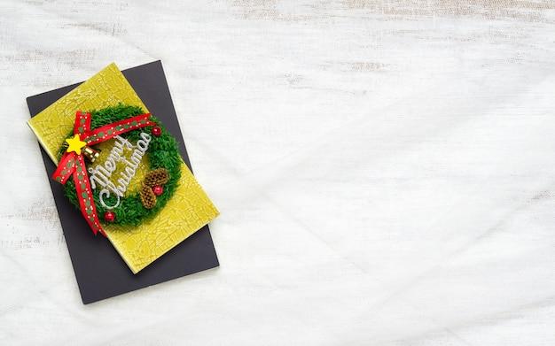 Sinal de feliz natal no notebook no ninho de tecido em madeira branca
