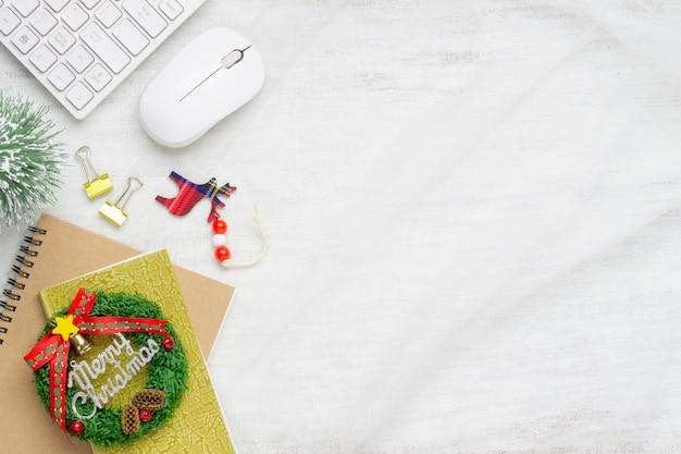 Sinal de feliz natal no notebook, teclado e mouse em tecido na madeira