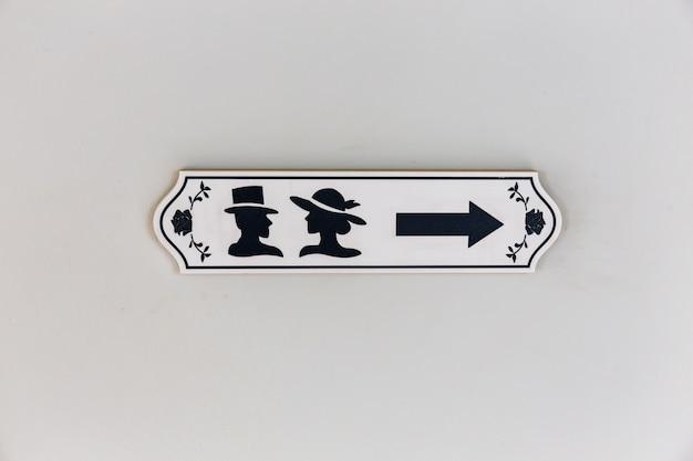 Sinal de ícone de sanitários de madeira com símbolo masculino e feminino e seta de direção