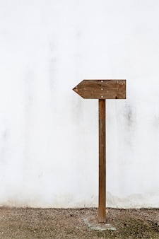 Sinal de indicação de madeira vazio em uma parede branca