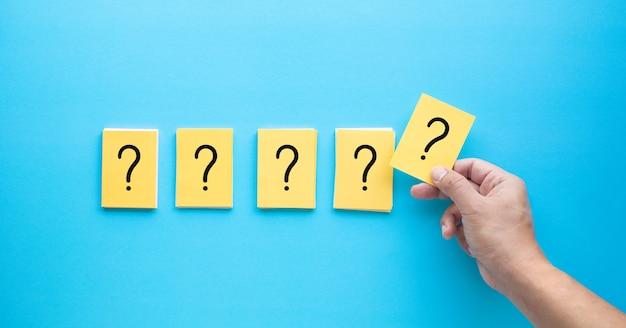 Sinal de interrogação e conceitos de resposta em papel timbrado com a mão da pessoa