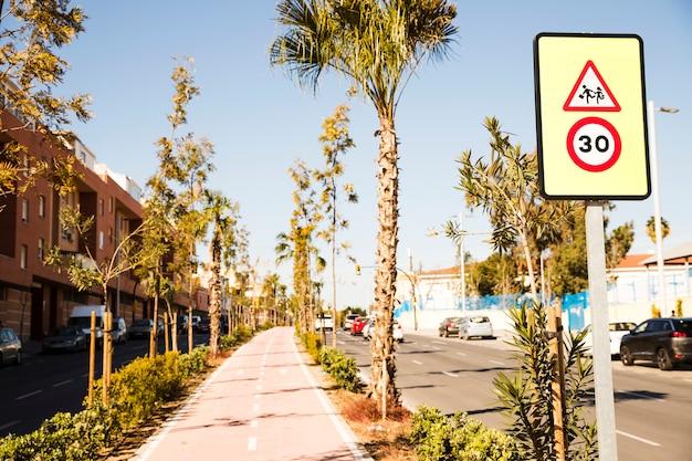 Sinal de limite de velocidade 30 na rua da cidade e ciclovia com árvores verdes