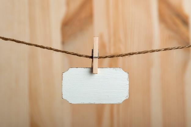 Sinal de madeira em branco pendurar com prendedores de roupa na corda em fundo de madeira. copie o espaço. lugar para o seu texto.