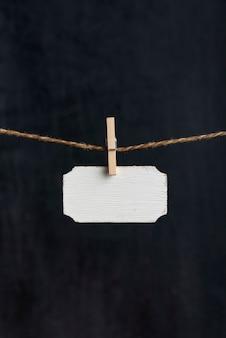 Sinal de madeira em branco pendurar com prendedores de roupa na corda em fundo preto. placa de identificação pequena. copie o espaço. quadro vertical.