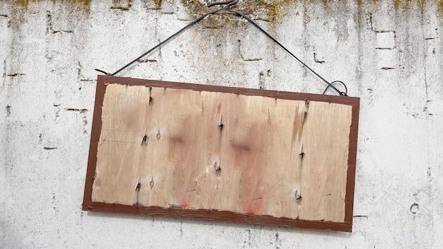 Sinal de madeira pendurado em uma parede de concreto cinza. quadro em uma parede de cimento. uma grande placa de madeira pendurada em uma corda com uma parede de concreto. copie o espaço.