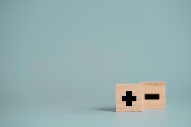 Sinal de mais na frente do sinal de menos que imprime a tela em um bloco de cubo de madeira e copia o espaço
