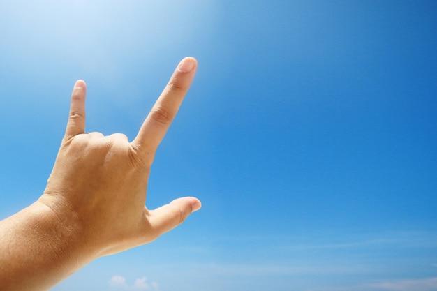 Sinal de mão de amor e mostrando os dedos significa que eu te amo no céu azul com luz solar