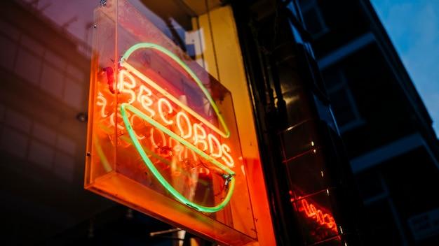 Sinal de néon colorido brilhando à noite atrás de discos de vidro