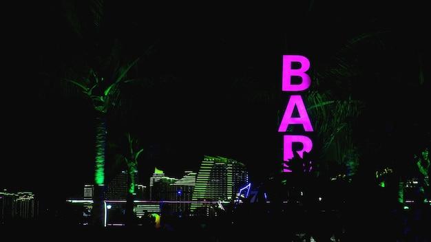 Sinal de néon rosa da palavra bar em um fundo preto.