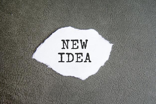 Sinal de nova idéia no papel rasgado no fundo cinza, conceito de negócio