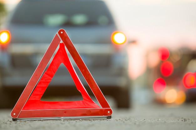 Sinal de parada do triângulo de emergência vermelho e carro quebrado na rua da cidade.