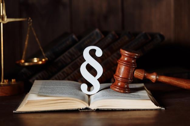 Sinal de parágrafo e martelo do juiz com livro em um tribunal