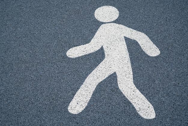 Sinal de pé, placa de rua de pedestres em um piso de asfalto escuro molhado