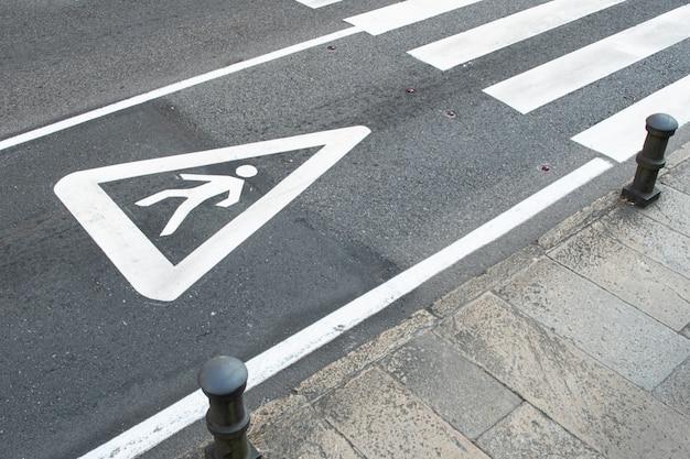 Sinal de pedestre pintado no asfalto de uma estrada da cidade. conceito de passadeira