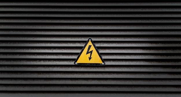Sinal de perigo amarelo em uma parede listrada preta