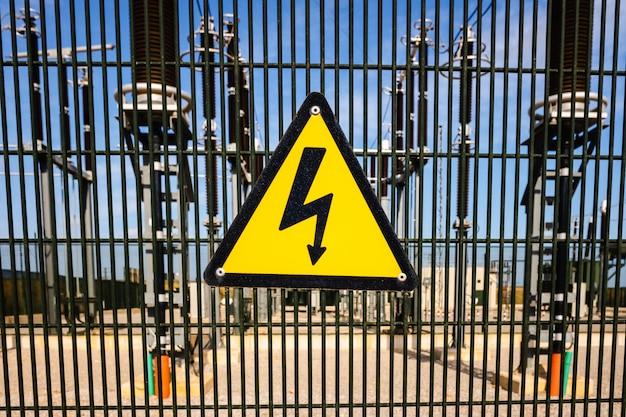 Sinal de perigo por eletrocussão na frente de uma instalação de transformadores elétricos.