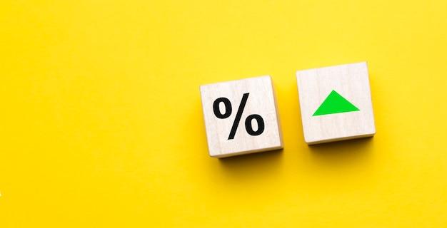 Sinal de porcentagem em cubos de madeira contra um fundo amarelo com espaço de cópia. conceito de venda e desconto.