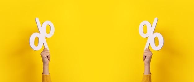 Sinal de porcentagem em mãos sobre fundo amarelo, imagem panorâmica